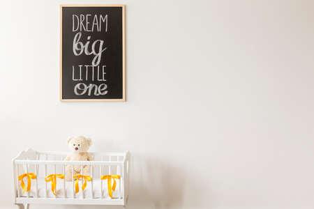 little one: Dream big little one on the blackboard in baby room Stock Photo
