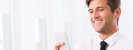 businessman in office: Smiling handsome businessman using his cellphone, panorama