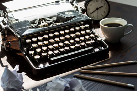 scribe: Shot of a classic retro typewriter and rolled up pieces of paper on a wooden table