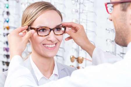 trying: Young woman trying on glasses in optical store
