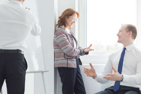 work environment: Smiling business people during presentation- positive work environment