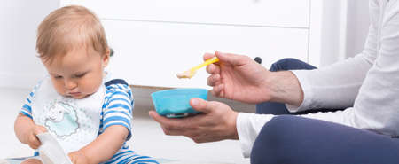 parental love: Father feeding his baby, holding a small bowl and a spoon, panorama