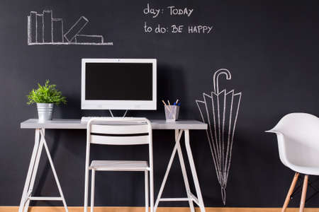 chalky: Minimalistic desk with computer and chairs against blackboard wall with chalky drawings Stock Photo