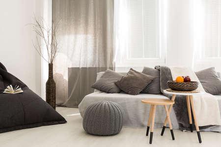 Disparo de un interior confortable sala de estar con un taburete de madera utilizado como una mesa de café Foto de archivo
