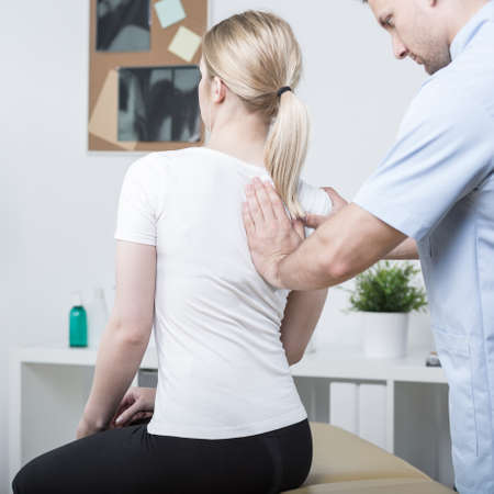 Chiropractic doing spinal mobilisation in physiotherapist's office Stock Photo