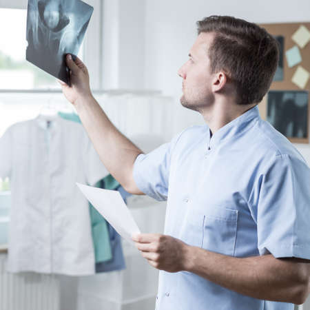 color therapist: Male experienced physiotherapist checking the xray photo