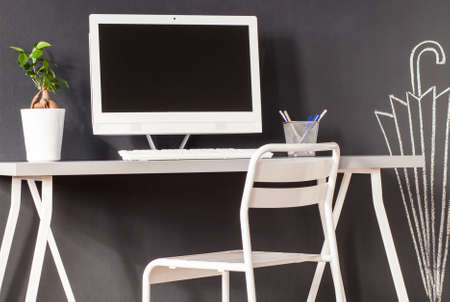 chalky: Minimalistic desk with computer and a chair against blackboard wall with chalky drawings Stock Photo