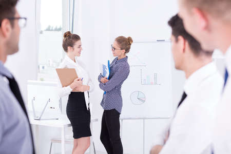 workgroup: Shot of a two smiling businesswomen talking to each other in the office Stock Photo