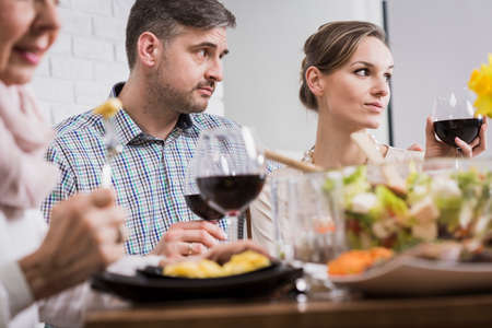 perplexed: Man and woman are looking perplexed at someone during a family dinner