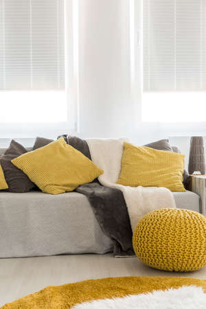 cropped shot: Cropped shot of a modern sofa with grey and yellow pillows and a grey throw Stock Photo