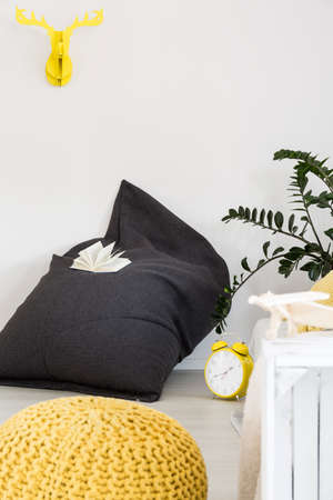 side table: Shot of a minimalist interior with a bag chair, yellow pouf and handmade side table Stock Photo