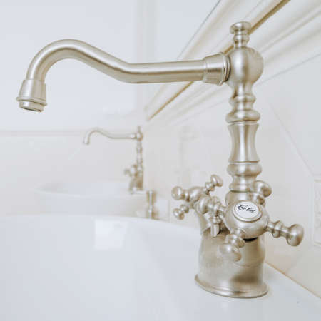 handbasin: Decorative faucets in white and stylish bathroom Stock Photo