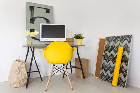 bright paintings: Shot of a minimalist workplace with grey desk and yellow office chair
