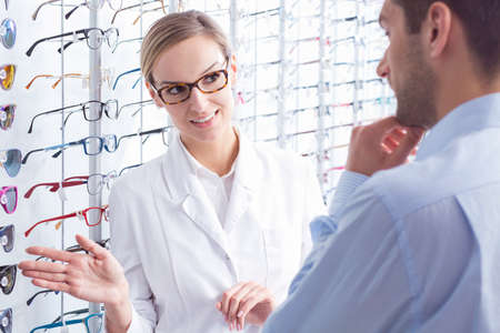 optician: Young optician client is choosing prescription glasses