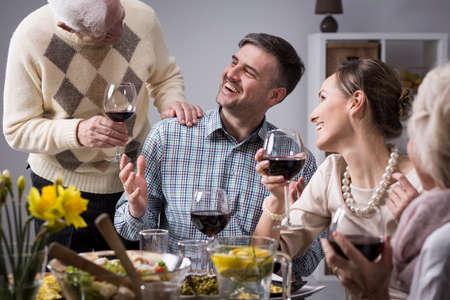 Au cours d'un dîner en famille, un homme plus âgé touche une épaule d'un homme plus jeune