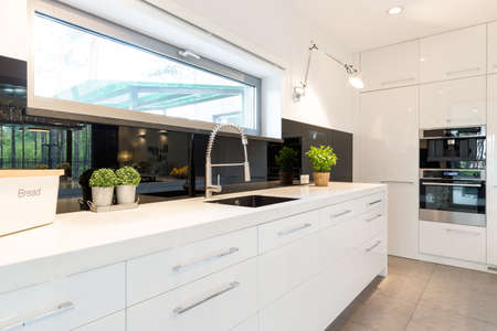Modern house- spacious white kitchen with white worktop Foto de archivo
