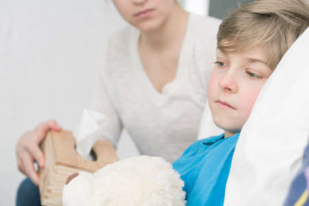 handkerchiefs: Close-up of a little boy with fever, lying in bed and his mum holding a box of handkerchiefs in the blurry background Stock Photo