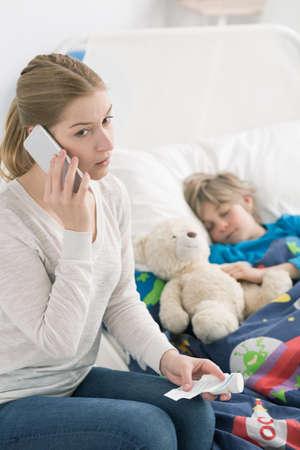 niños enfermos: madre preocupante que se sienta junto a un escolar por enfermedad del sueño, llamar al médico