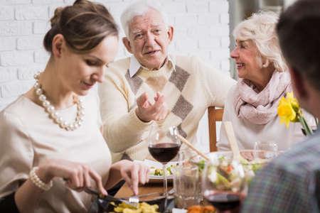 el hombre mayor le explica algo en la mesa de la familia durante la cena