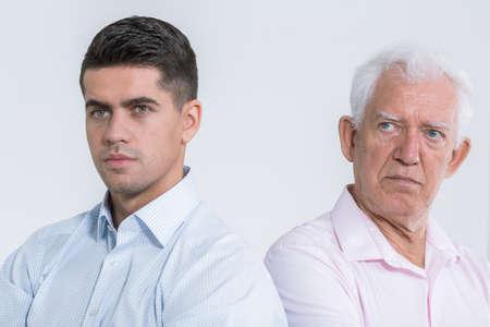 Schuss von wütenden Vater und unglücklich Sohn in eine Richtung schauend Standard-Bild