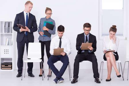 supervisores: Disparo de un candidatos de trabajo que realizan una prueba de evaluación previa, mientras que los supervisores están buscando por encima del hombro