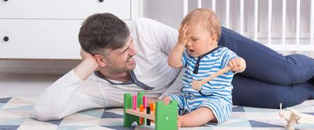 Père couché sur un plancher et jouer avec son petit bébé, panorama