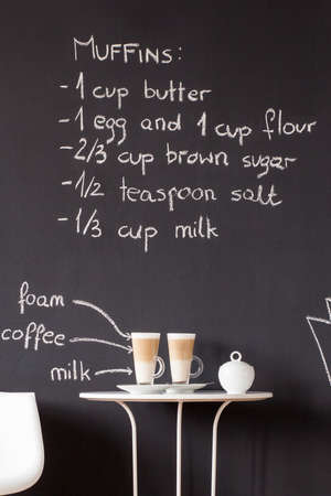 chalky: Minimalistic coffee table with two glasses of coffee and sugar-bowl against blackboard wall and chalky muffins recipe