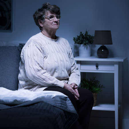 persona sentada: Disparo de una anciana sentada sola en una habitación por la noche