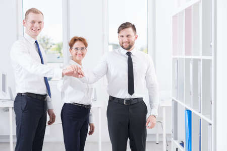 informal clothing: Partnership at work- business team holding hands together Stock Photo