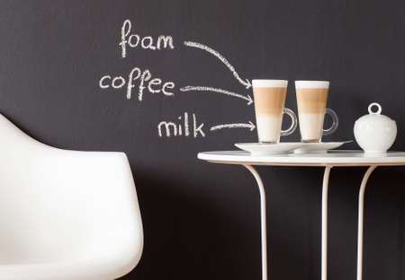 black boards: Coffee table with a chair and glasses of coffee and sugar-bowl against blackboard wall Stock Photo