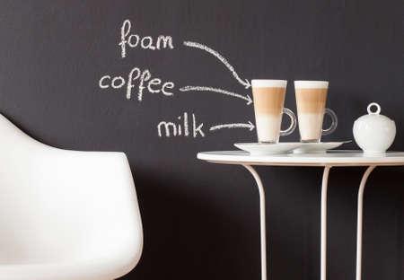decoracion mesas: Mesa de centro con una silla y vasos de café y azúcar-bol contra la pared de la pizarra