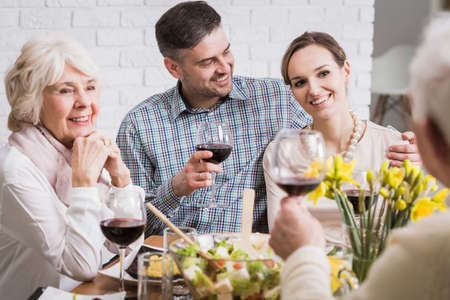 tenderly: Man tenderly embraces his wife during a family dinner