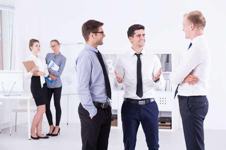 백그라운드에서 여성을 관찰하는 동안 사무실에 서 서 얘기 하 고 웃는 남성 동료의 총