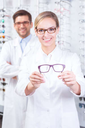 optician: Beautiful female optician in uniform holding glasses frame
