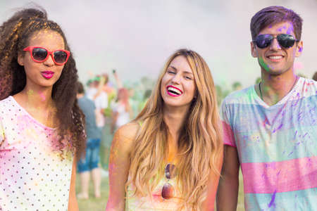 cropped shot: Cropped shot of three friends covered with a powder paint at a color festival