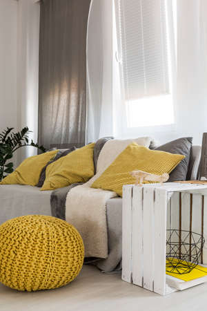 Shot of a minimalist living room interior with a comfortable sofa and yellow pouf