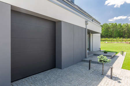 garage on house: Close-up of garage door and driveway of modern house