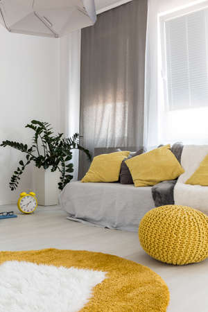 grey rug: Shot of a comfortable room interior, designed in grey and yellow colors Stock Photo