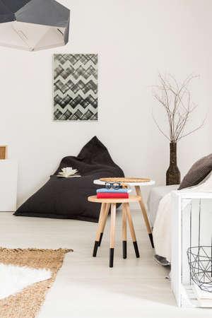 Shot von einem hellen Zwischen mit einer schwarzen Tasche Stuhl und einem handgemachten weißen Beistelltisch