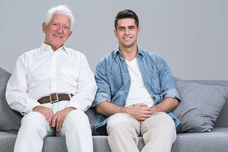 kin: Cropped shot of a happy father sitting on the sofa with his adult son Stock Photo