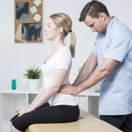 mobilization: Young physiotherapist doing lumbar spine mobilization