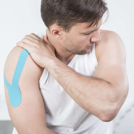 taping: Picture of athletic man with arm pain during kinesiotherapy
