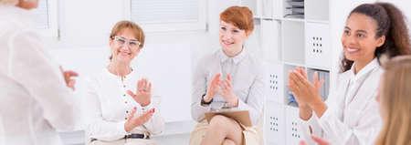 respetar: Grupo de mujeres felices las palmas de sus manos, sentado en la luz entre otras, panorama