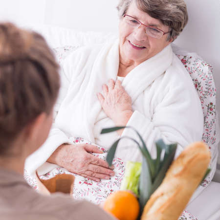 Friend with shopping visiting older woman lying in hospital bed