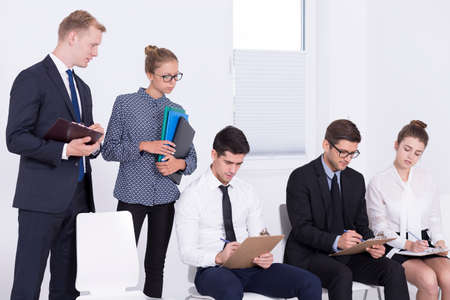 company job: Shot of recruiters standing behind job candidates and looking over their shoulders Stock Photo