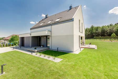 Simple moderna casa exterior con un bonito césped verde Foto de archivo