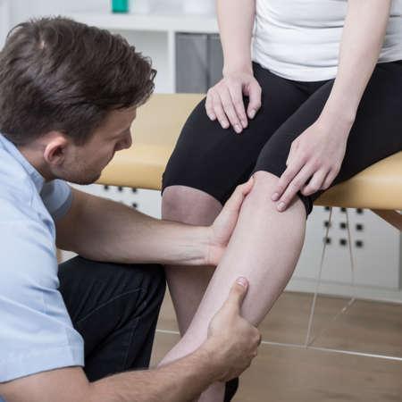 luxacion: El diagnóstico de paciente joven fisioterapeuta con la rodilla dolorosa