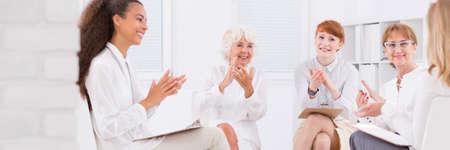 personas reunidas: Grupo de mujeres de negocios feliz aplaudiendo sus manos, sentado en la luz entre otras, panorama