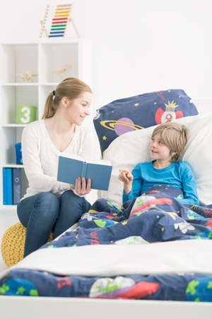 Smiling mother reading a book to her little son who is lying ill in bed