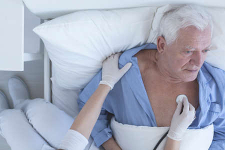 a medical examination: Shot of a nurse doing a medical examination using the stethoscope of senior patient lying on a hospital bed Stock Photo